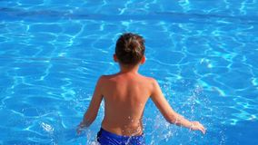 Happy boy jumping into the blue water pool. Slow motion. In 180 fps stock video