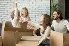 Happy boy jumping from box playing with family packing together. Happy kid boy jumping out of cardboard box playing with family while packing together preparing Royalty Free Stock Photos