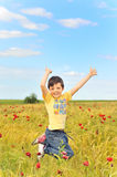 Happy boy jumping on field Stock Photos
