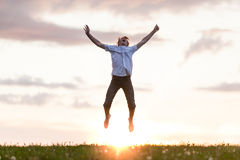Happy Boy Jumping at the Ground Against Sunset Royalty Free Stock Images