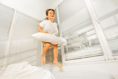 Happy boy jumping on his bad with white pillow Royalty Free Stock Images