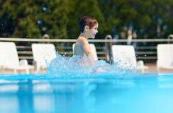Happy boy jumping in the pool Royalty Free Stock Photos