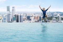 Happy Boy Jumping Into The Pool Stock Photo