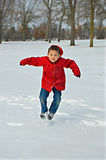 Happy Boy Jumping, Red Coat in Winter Stock Photos