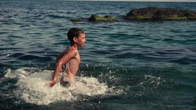 Happy boy is jumping into the sea water during summer holidays. Slow motion.