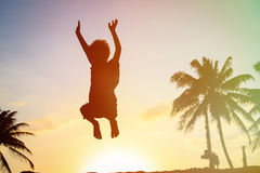 Happy boy jumping at sunset beach Royalty Free Stock Photography