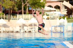 Happy boy jumping in swimming pool. Happy active child, blonde caucasian teenage boy, jumping and diving into swimming pool in tropical resort at sunset Royalty Free Stock Images