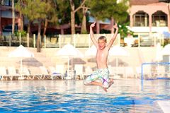Happy boy jumping in swimming pool. Happy active child, blonde caucasian teenage boy, jumping and diving into swimming pool in tropical resort at sunset Royalty Free Stock Photography