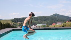 Happy boy jumping into swimming pool
