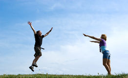 Happy boy jumping to girl. Happy boy jumping to girl on the meadow Royalty Free Stock Photography