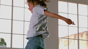Happy boy jumping up and down in front of window Royalty Free Stock Images
