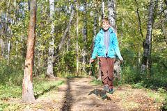 Happy boy jumps with skipping rope. In forest on sunny day royalty free stock photography