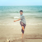 Happy boy kicking a football on the beach Stock Image