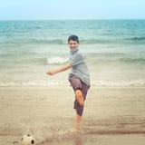 Happy boy kicking a football on the beach Stock Image