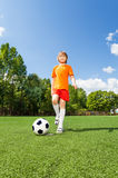 Happy boy kicking football with his leg Stock Images