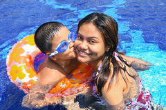 Happy boy kiss Mom in the pool. Happy boy kiss Mom in the swimming pool Royalty Free Stock Photos
