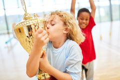 Happy boy kisses a cup. After a competition in physical education royalty free stock image