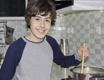 Happy Boy is in kitchen on a stove cooking soup Royalty Free Stock Photos