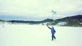 Happy boy with a kite. Winter landscape.