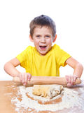 Happy boy kneads and rolling dough for pie on kitchen table Royalty Free Stock Photo