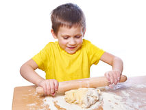 Happy boy kneads and rolling dough for pie on kitchen table Stock Photography