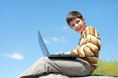 Happy boy with a laptop Stock Photos