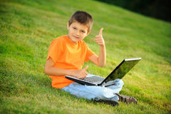 Happy boy with laptop. Schoolboy with laptop is sitting on the grass Royalty Free Stock Photos