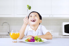 Boy laughing at green broccoli in kitchen Stock Photos