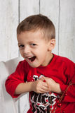 Happy boy laughing. Young boy sitting in chair in studio, smiling with red shirt and wood background Royalty Free Stock Photos