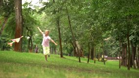 Happy boy launching kite in park, leisure activity outdoors, carefree childhood royalty free stock image