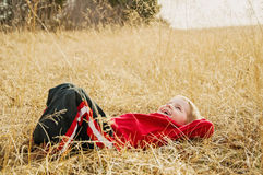 Happy boy laying relaxed in a field Stock Photo