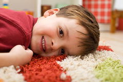 Happy boy laying on a rug Stock Image