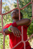 Happy boy leaning on net during obstacle course Royalty Free Stock Photos