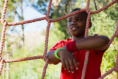Happy boy leaning on net during obstacle course Royalty Free Stock Photo