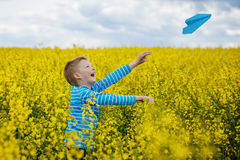 Happy boy leaning and throwing blue paper airplane on bright sun Royalty Free Stock Photography