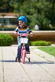 Happy boy learning to ride his first bike Stock Photo
