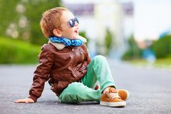 Happy boy in leather jacket posing on the ground Stock Photography