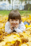 Happy boy in leaves of autumn lies Royalty Free Stock Photos