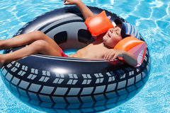 Happy boy lies with eyes closed on wheel in pool. Happy boy lies with eyes closed on wheel shaped inflatable mattress in pool royalty free stock image
