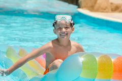 Happy boy on lilo in pool. Happy young boy playing on lilo in swimming pool Royalty Free Stock Photo