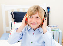 Happy boy listening music sitting on bed Stock Images