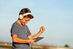 Happy boy listening to music on digital tablet. Royalty Free Stock Photography