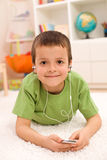 Happy boy listening to music laying on the floor Royalty Free Stock Images