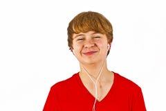 Happy boy listening to music. Via earphone Stock Photos
