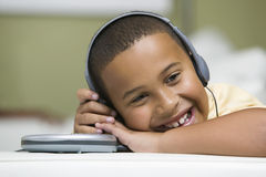 Happy Boy Listening To Portable CD Player. Closeup of a happy relaxed boy listening to portable CD player on sofa Stock Images
