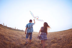 Happy boy and little girl running with bright kite on a meadow. In a sunny evening royalty free stock images