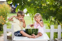 Happy boy and little girl with watermelon lying. This image has attached release Stock Photos