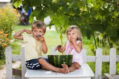 Happy boy and little girl with watermelon lying Royalty Free Stock Images