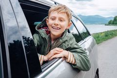 Happy boy look out from auto window Royalty Free Stock Images