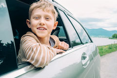 Happy boy look out from window car Stock Image